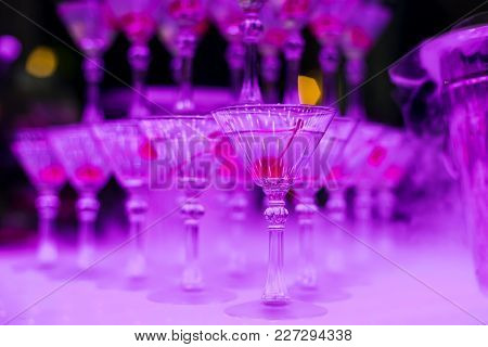 Martini Glasses With Sweet Cherry Close - Up With Pink Illumination