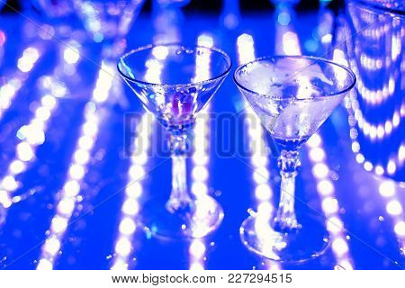 Empty Martini Glasses At Night Club At Party With Focus In The Foreground