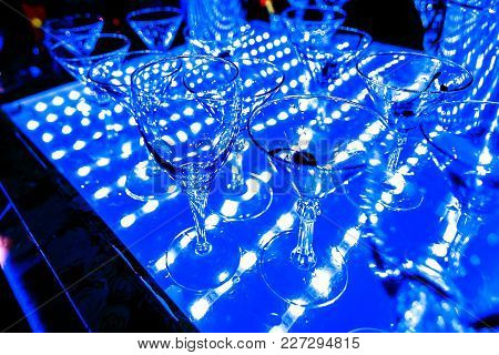 Empty Martini And Champagne Glasses At A Night Party In A Brightly Lit Restaurant