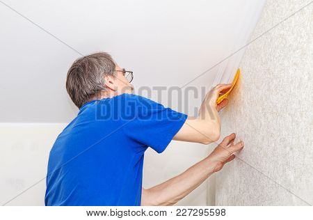 Elderly Worker With Spatula Smoothing Wallpaper In His House