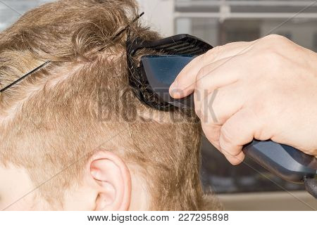 Fragment Of Head Of Young Man During Shearing By Means Of Electric Hair Clipper Closeup At Selective