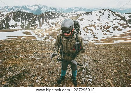 Man With Helmet And Ice Axe Climbing In Mountains Travel Lifestyle Survival Concept Adventure Outdoo