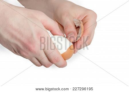 Boiled Brown Chicken Egg In Human Hands During Cleaning From Eggshell On A White Background