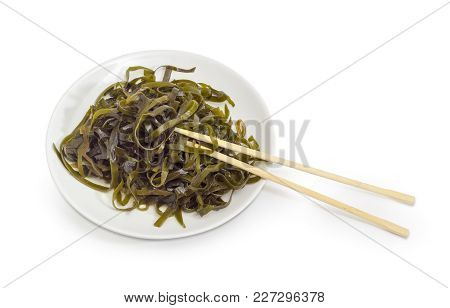 Salad Of Marinated Sliced Laminaria With Vegetable Oil And Spices On The White Dish With Bamboo Chop