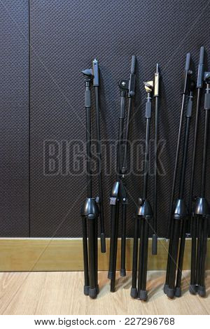 A group of black microphone stands inside a studio sound booth