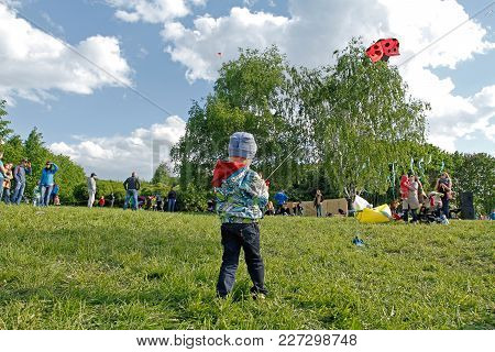 Moscow, Russia - May 27, 2017: Boy Launches Ladybug Kite Into The Sky At The Kite Festival In The Pa