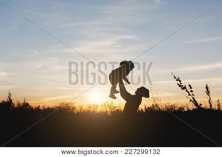 Silhouette Of Woman High Toss Up Little Cute Child Baby Boy On Nature, Sunset Horizon Background. Mo