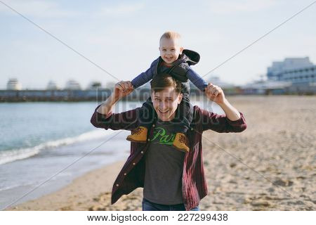 Man Playing At Sea Sand Beach Background With Little Cute Child Baby Boy, Good Mood. Father Keeps On
