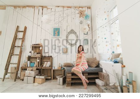 Happy Pregnant Young Brunette Woman In Striped Long Dress With Big Belly In Decor Room, Tummy, Teddy