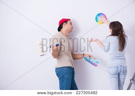 Young family doing renovation at home  - painting walls