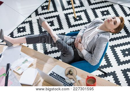 High Angle View Of Attractive Young Businesswoman Relaxing In Chair At Office
