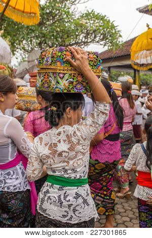 Bali, Indonesia - September 17, 2016: Unidentified balinese woman in traditional dress sarong with religious offering during Galungan celebration in Bali.