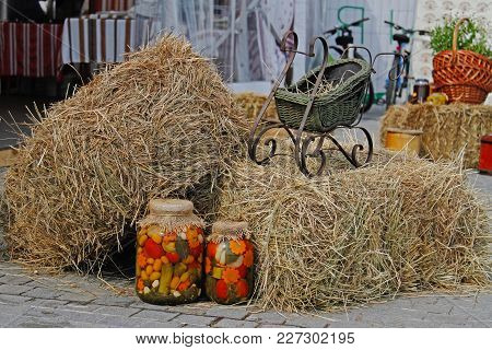 Marinated And Canned Vegetables In Glass Jars Standing Near The Hayloft With A Decorative Cart