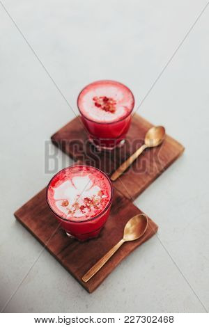 Two Trendy Beetroot Lattes With Latte Art And Flower Petals On Foam.