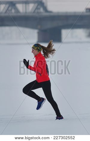 Young Female Athlete Running In Winter Through The Snow, Sport And Leisure Concept
