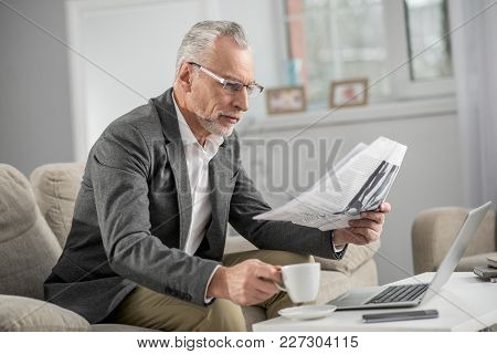 Press Checkup. Serious Pensioner Wearing Glasses And Taking Cup With Coffee, Sitting In Semi Positio