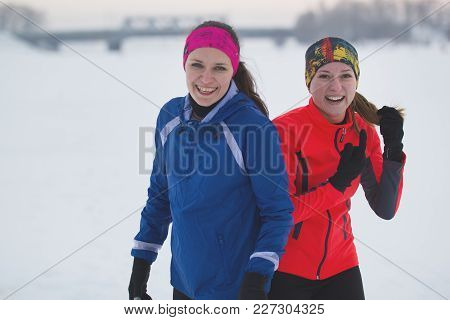 Two Young Female Athletes Is Posing In Winter Ice Field, Sport And Leisure Concept