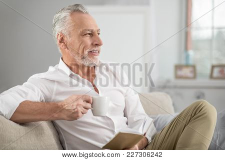 Coffee Break. Attractive Mature Man Keeping Smile On His Face And Holding Cup In Right Hand While Ha