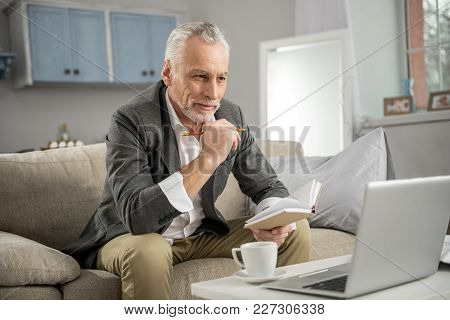 Thoughtful Mood. Handsome Male Person Keeping Smile On His Face And Leaning Elbows On Knees While Lo