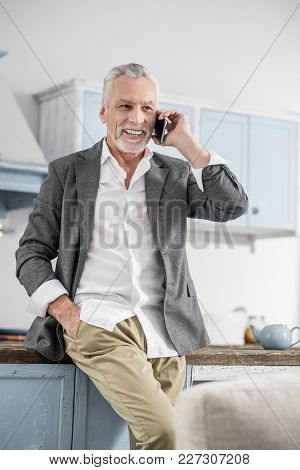 Be Joyful. Cheerful Man Expressing Positivity And Keeping Right Hand In The Pocket While Being At Ho