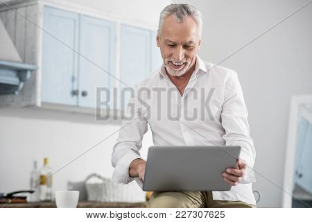Being Glad. Happy Mature Man Keeping Smile On His Face And Holding Laptop While Reading Message