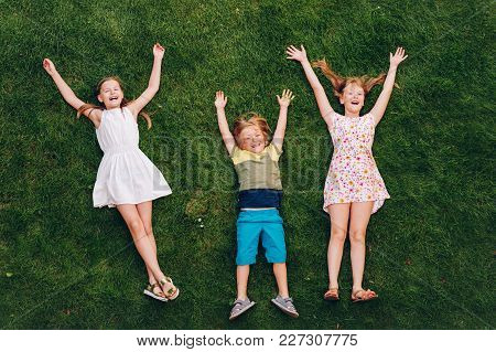 Happy Children Having Fun Outdoors. Kids Playing In Summer Park. Little Boy And Two Girls Lying On G
