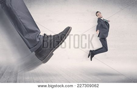 Big foot in a black shoe fire small, young, businessman who is flying away in the space