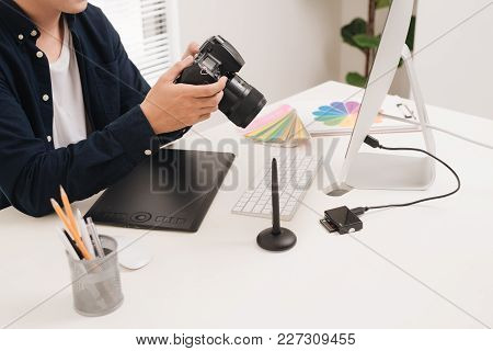Male Photographer, Sitting At His Desk, Looking To Camera