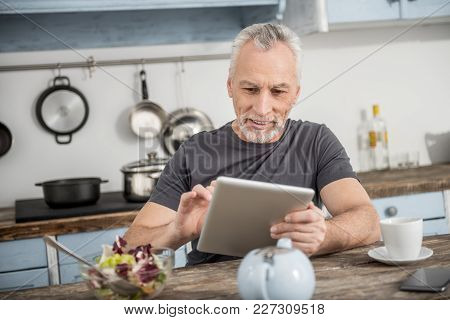 Working Process. Cheerful Grey-haired Man Keeping Smile On His Face And Leaning Elbows On The Table