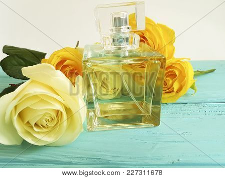 perfume bottle with yellow roses on a wooden