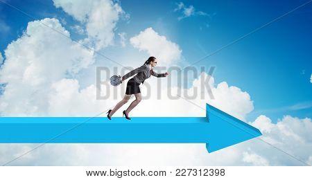 Businesswoman walking on arrow sign