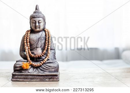 Buddha Statue With Beads. Buddha Statue In Bright Room.