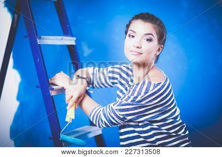 Beautiful young woman doing wall painting, standing on ladder. Beautiful young woman
