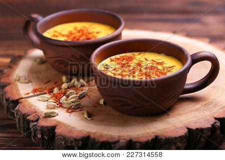Traditional Indian Cuisine. Turmeric Milk With Cinnamon, Saffron, Cardamom And Turmeric On Black Sla