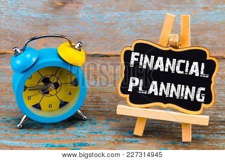 Alarm Clock And A Blackboard With  Text - Financial Planningб, On Wooden Background.