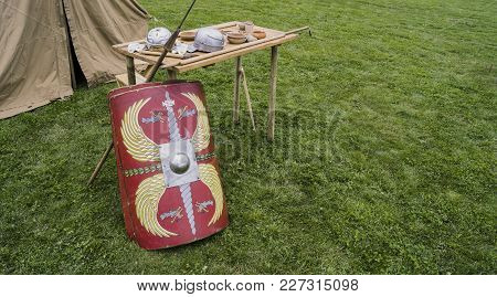 Ancient Roman Soldier Equipment (roman Shield, Roman Spear, Roman Helmet) Stacked On Wooden Table