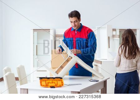 Contractor repairman assembling furniture under woman supervision