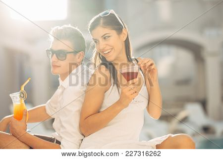 Two Attractive People Having Cocktails By The Pool In The Summer Vacation Resort.pool Lounge Bar Par