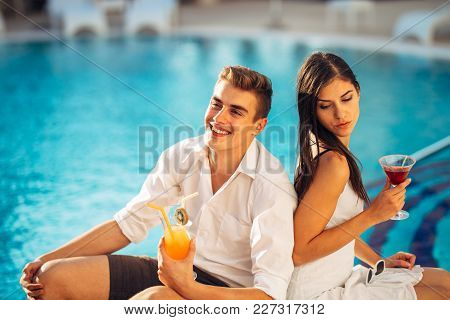 Attractive Couple Enjoying Summer Vacation Near The Pool In Exotic Vacation Resort.attending Summer