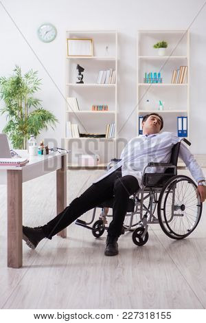 Doctor resting on wheelchair in hospital after night shift