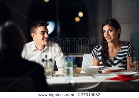 Group Of Friends Having A Dinner In A Restaurant.double Date.attractive People Night Out,dining In A