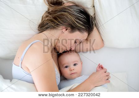 Young Mother Breastfeeds Her Baby, Holding Him In Her Arms And Smiling