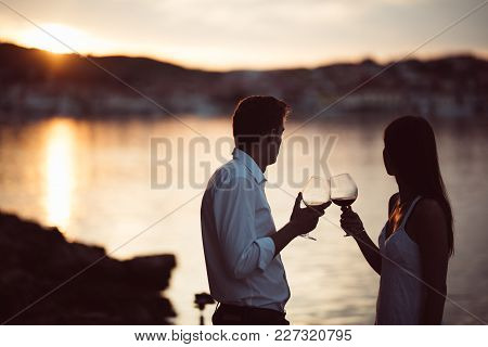 Two Young People At The Beach,making A Toast For Special Occasion.looking At The Sun,enjoying The Vi