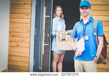 Smiling delivery man in blue uniform delivering parcel box to recipient - courier service concept. Smiling delivery man in blue uniform