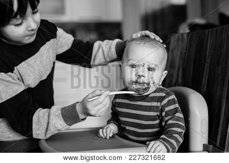 Cute Preschool Boy, Feeding His Baby Brother With Mashed Vegetables, Baby Eating Mashed Food For The