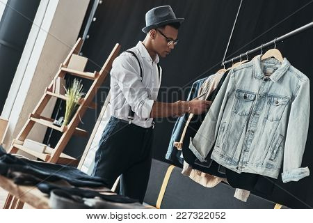 Searching For Inspiration. Thoughtful Young Man Choosing Clothes From The Rack While Standing In The