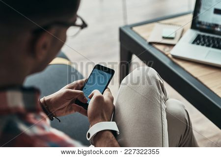 Another Message. Close Up Top View Of Young Man Using His Smart Phone While Sitting In The Creative
