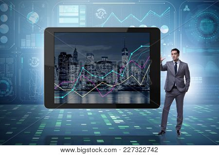 Businessman standing next to tablet computer in business concept