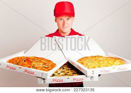 A Pizza Delivery Boy Is Showing Three Differen Pizzas