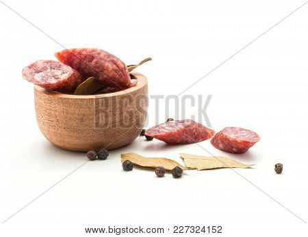 Sliced Hungarian Dry Sausages Pepperoni Pieces With Black Pepper And Bay Leaves In A Wooden Bowl Iso